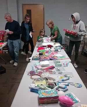 Volunteers pack shoeboxes at an Operation Christmas Child packing party at Grace United Methodist Church.
