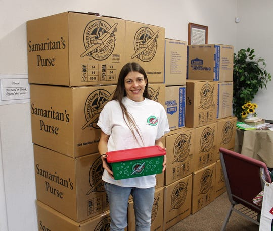 Tiffaney Alfaro of Grace Baptist Church stands with boxes of shoewboxes ready to be shipped to an Operation Christmas Child processing center.