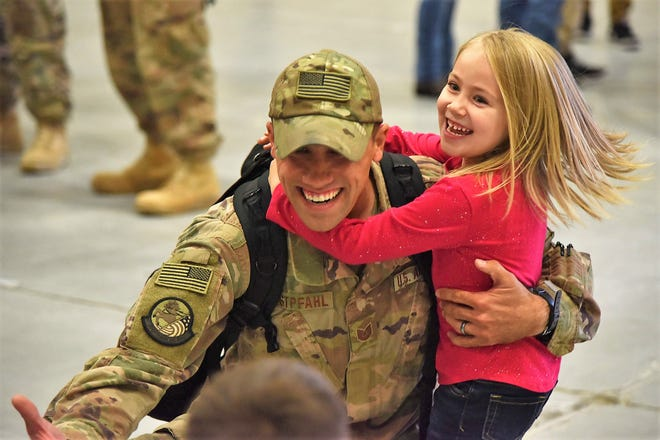 An Airman from the 819th Rapid Engineer Deployable Heavy Operational Repair Squadron Engineers (RED HORSE) hugs his children Nov. 5, 2018, at the airfields located on Malmstrom Air Force Base, Mont. The 819th RED HORSE U.S. Africa Command team shared in multi-agency base building efforts for Air Base 201 in Agadez, Niger, an expeditionary installation being constructed in one of the most remote regions in Africa.