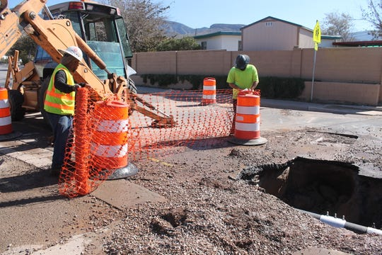 Jamarr Thompson and Eddie Barreras fence off an area of Bellamah Drive following repairs to a burst water main.