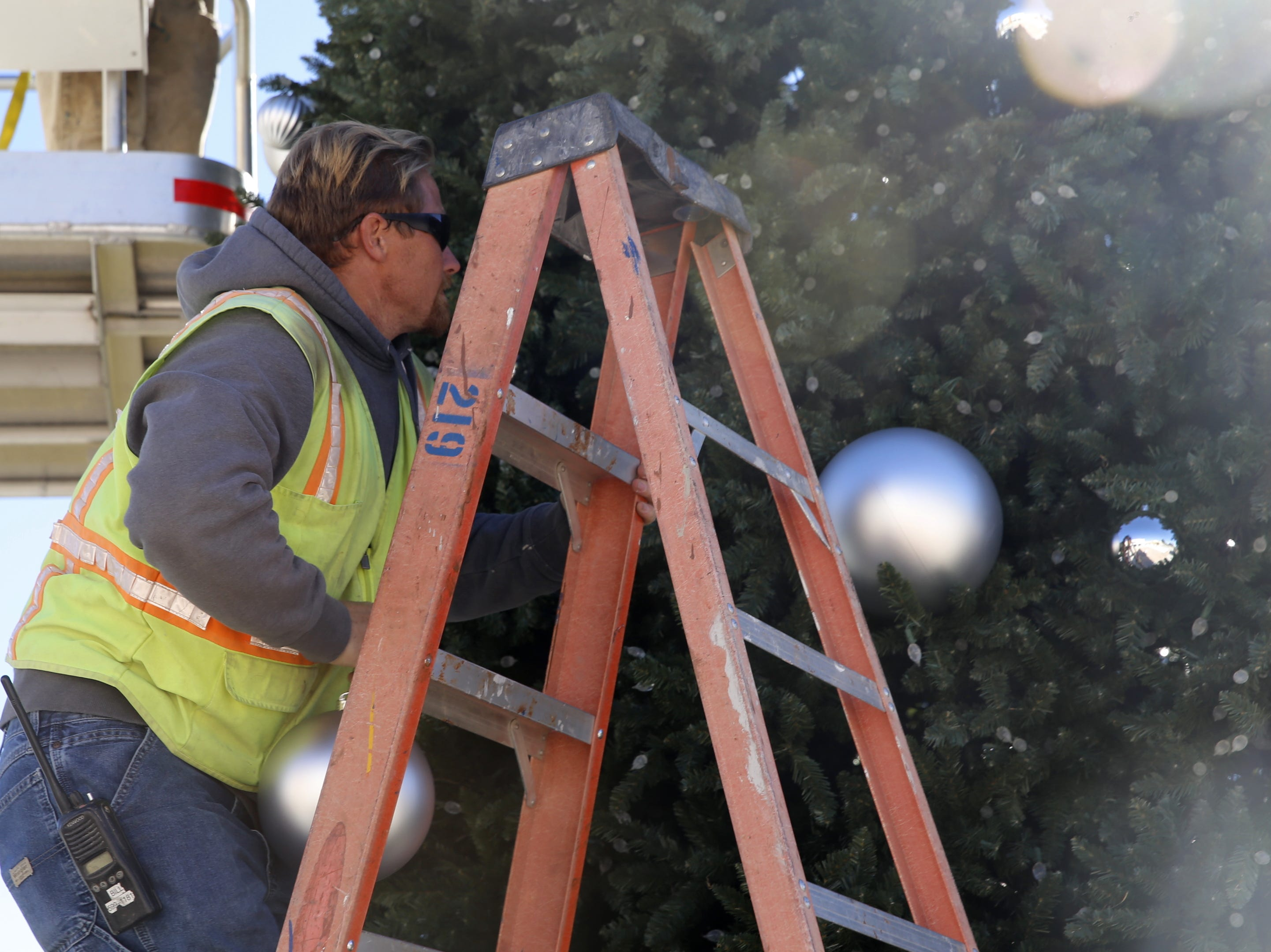 Bill Goelz climbs a ladder, Monday, Nov. 19, 2018, to hang an ornament on the Christmas tree outside the Farmington Civic Center.