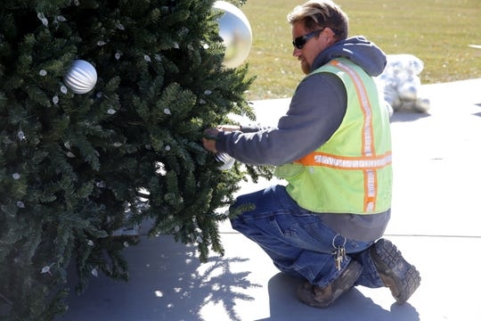 Bill Goelz hangs an ornament on the Christmas tree Monday at the Farmington Civic Center.