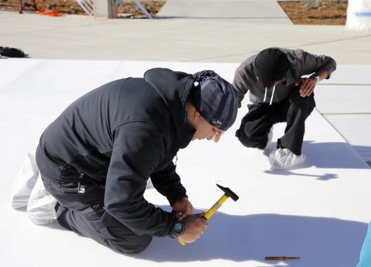 Darren Taylor helps install an ice skating rink Monday at the Farmington Civic Center.