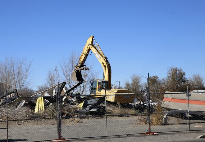 A former gas station is demolished Monday at the intersection of East Pinon Street and South Miller Avenue in Farmington.