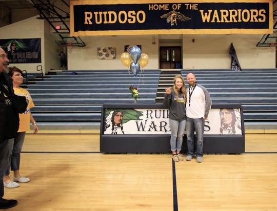Alexandra Michelena and Athletics Director Kief Johnson in the gym at Ruidoso High school celebrate her recent signing of a golf scholarship to San Angelo State University as her dad and step-mother look on with pride.