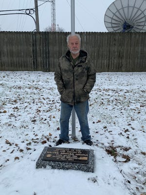 Westland resident Tom Kozak proudly stands behind a memorial tombstone honoring U.S. Navy radioman Walter E. Mintus. The marker is located at VFW Post 9885, in Westland.