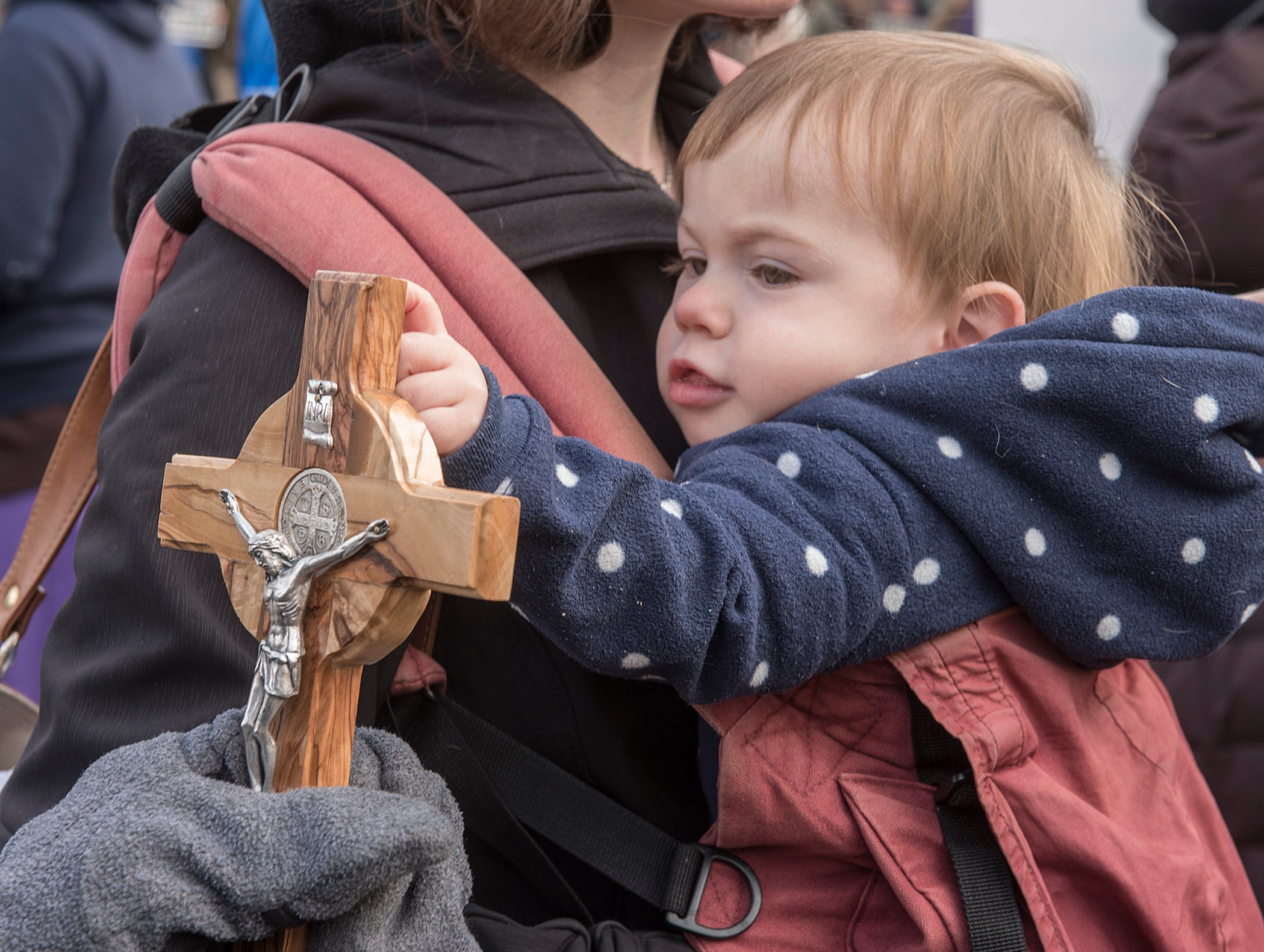 One year old Eamon Kovacs touches a crucifix held by an clinic protester. Eamon is held by his mother, Elizabeth Kovacs. They are from Harper Woods.