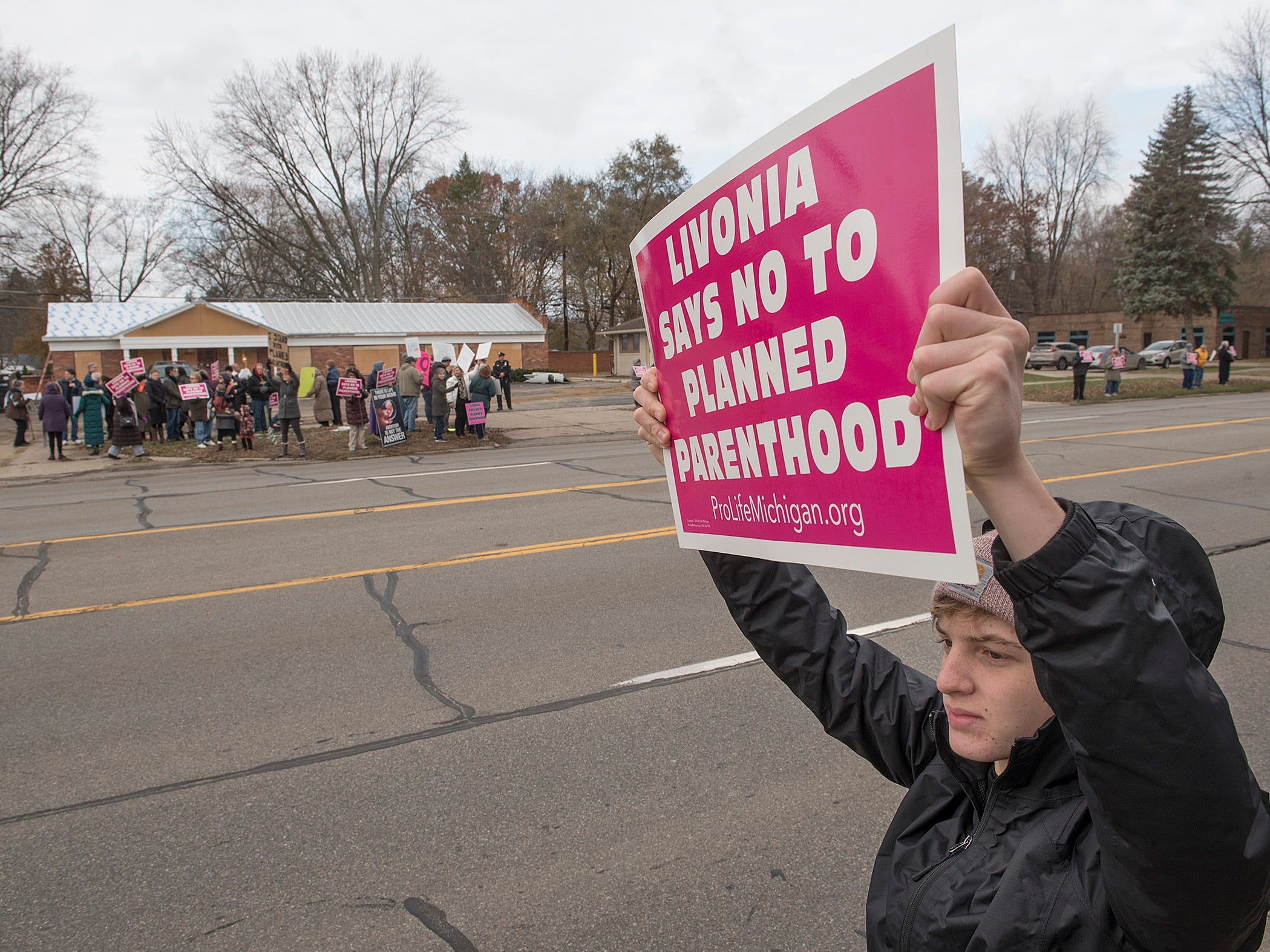 Paul Davenport, of Livonia. holds a sign protesting the Planned Parenthood faciity on Farmington Road, north odf Five Mile Road in Livonia.