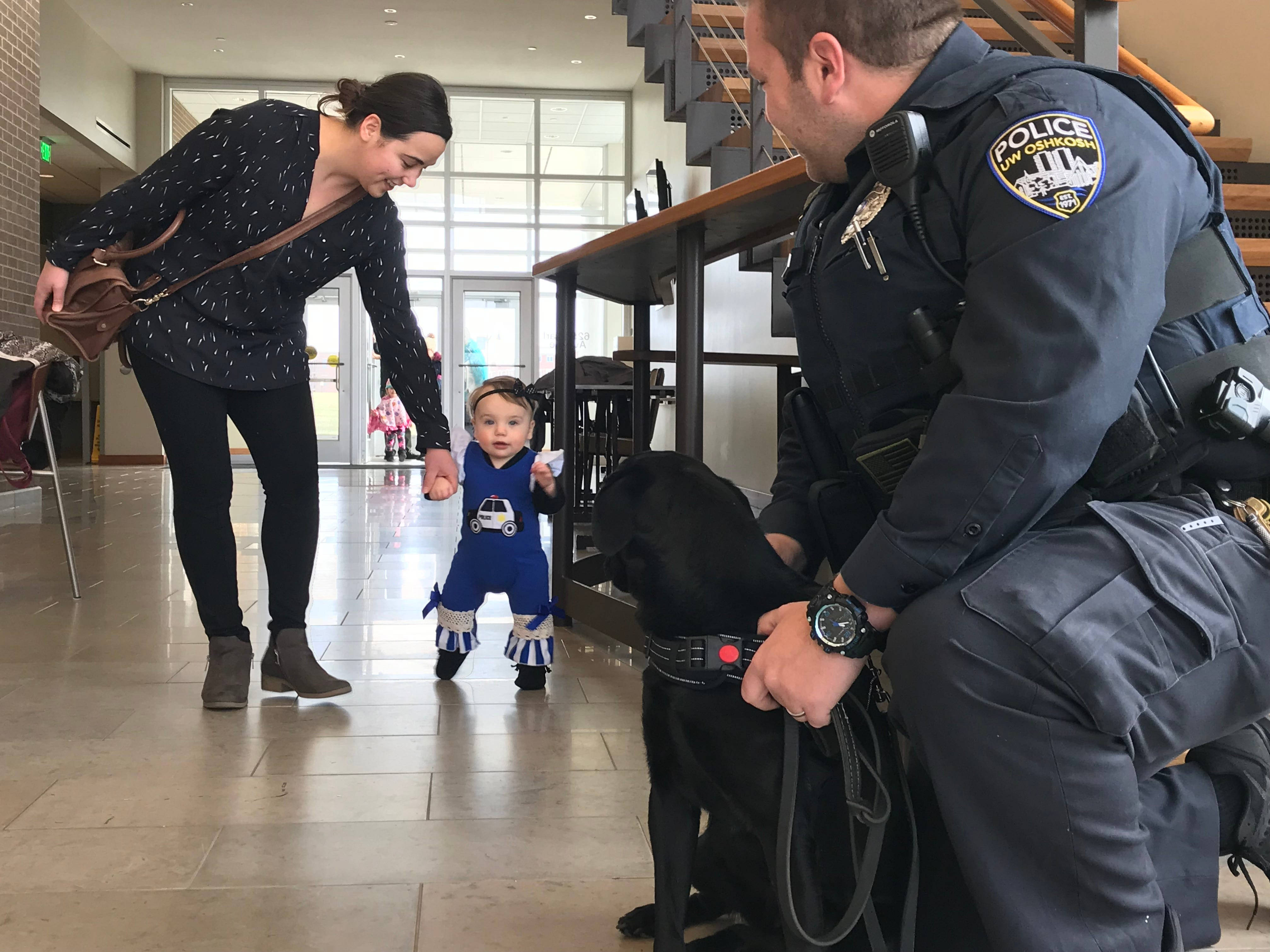 One-year-old Elspeth Kohlman arrives Monday at the swearing-in ceremony at the University of Wisconsin-Oshkosh to see her dog Skylar become a K-9 officer.