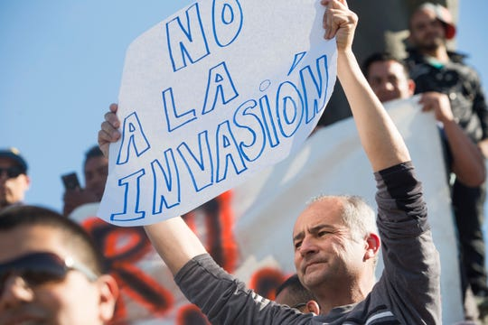 "A Tijuana resident shows his sign opposing an ""invasion"" by caravan migrants. Protesters marched towards the shelter where 2,400 migrants are being housed, then were stopped by Tijuana's municipal police."