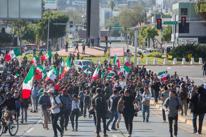 Tijuana residents march in opposition of the migrant caravan from Central America having arrived in their city.