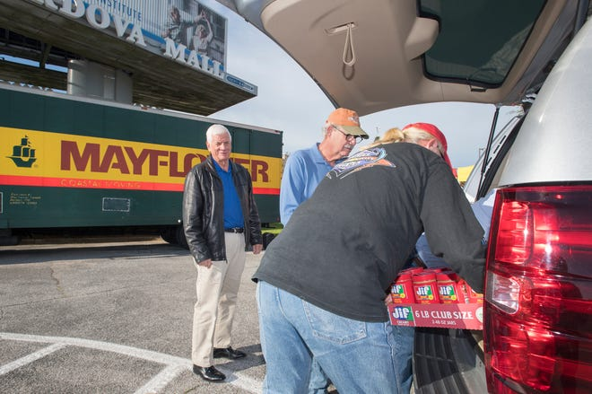 Bernie Mostoller, left, looks on as volunteers Chuck Lisner, center, and Frank Chestnut unload his donation during the annual Fill the Mayflower food drive for the Manna Food Pantry in Pensacola on Monday, November 19, 2018.  Manna is collecting non-perishable foods and cash donations in front of the Cordova Mall on Monday & Tuesday (November 19 & 20) from 7 am to 7 pm.