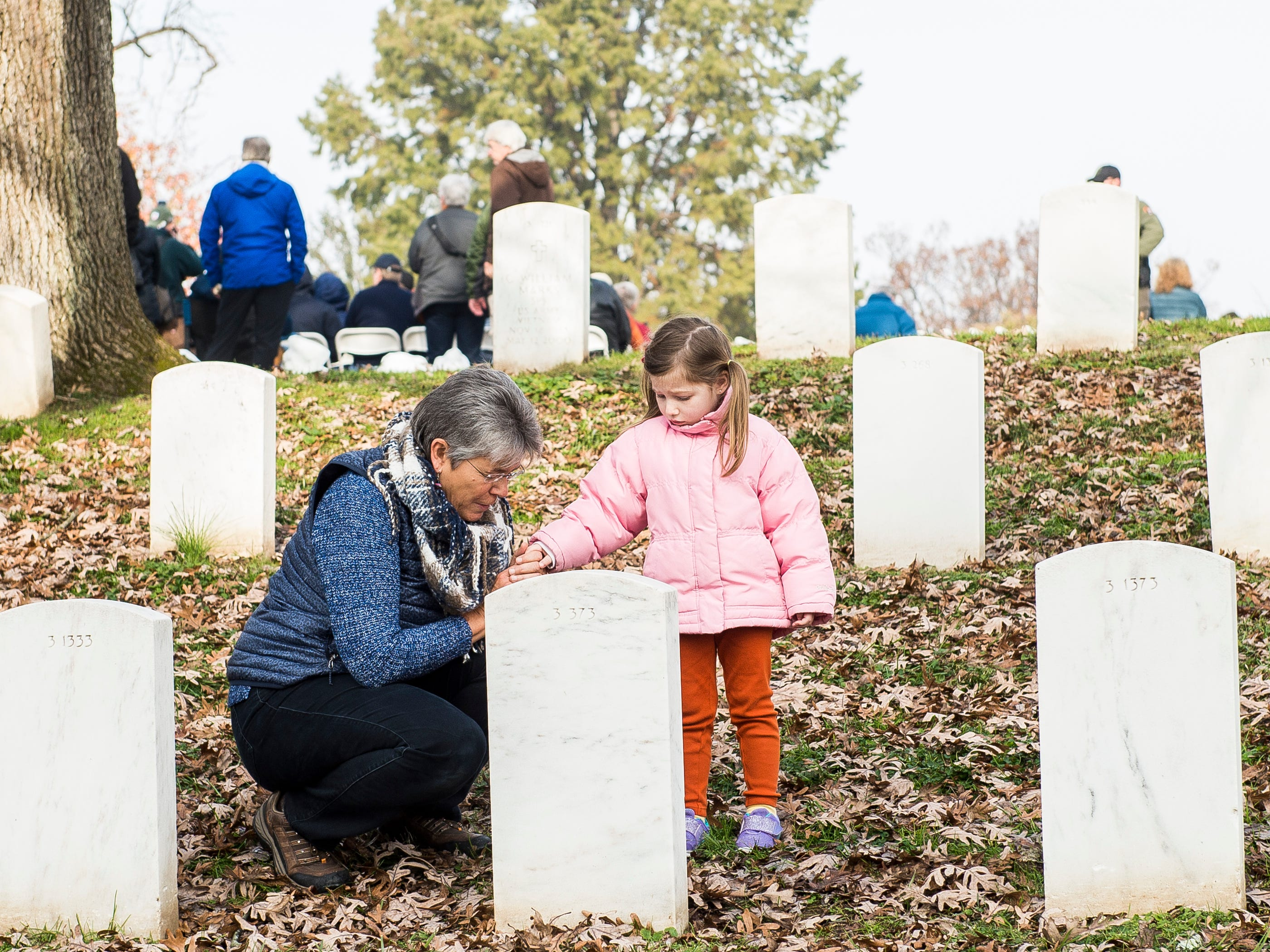 Nancy Kramer takes the hand of her four-year-old granddaughter, Charlotte Bohnenblust, as they visit graves in Gettysburg National Cemetery on Dedication Day Monday, November, 19, 2018.