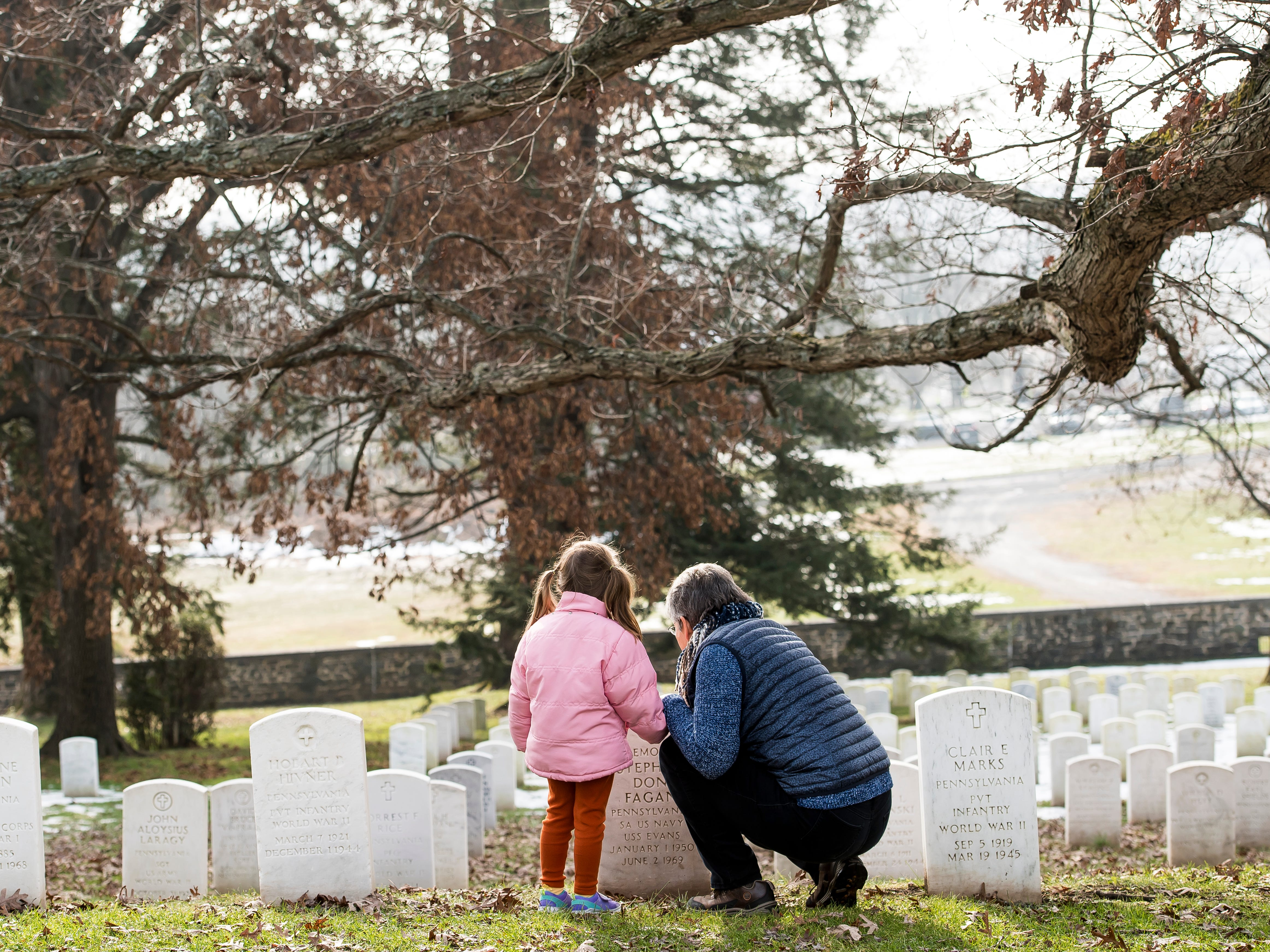 Nancy Kramer and her four-year-old granddaughter, Charlotte Bohnenblust, visit graves in Gettysburg National Cemetery during Dedication Day on Monday, November, 19, 2018.