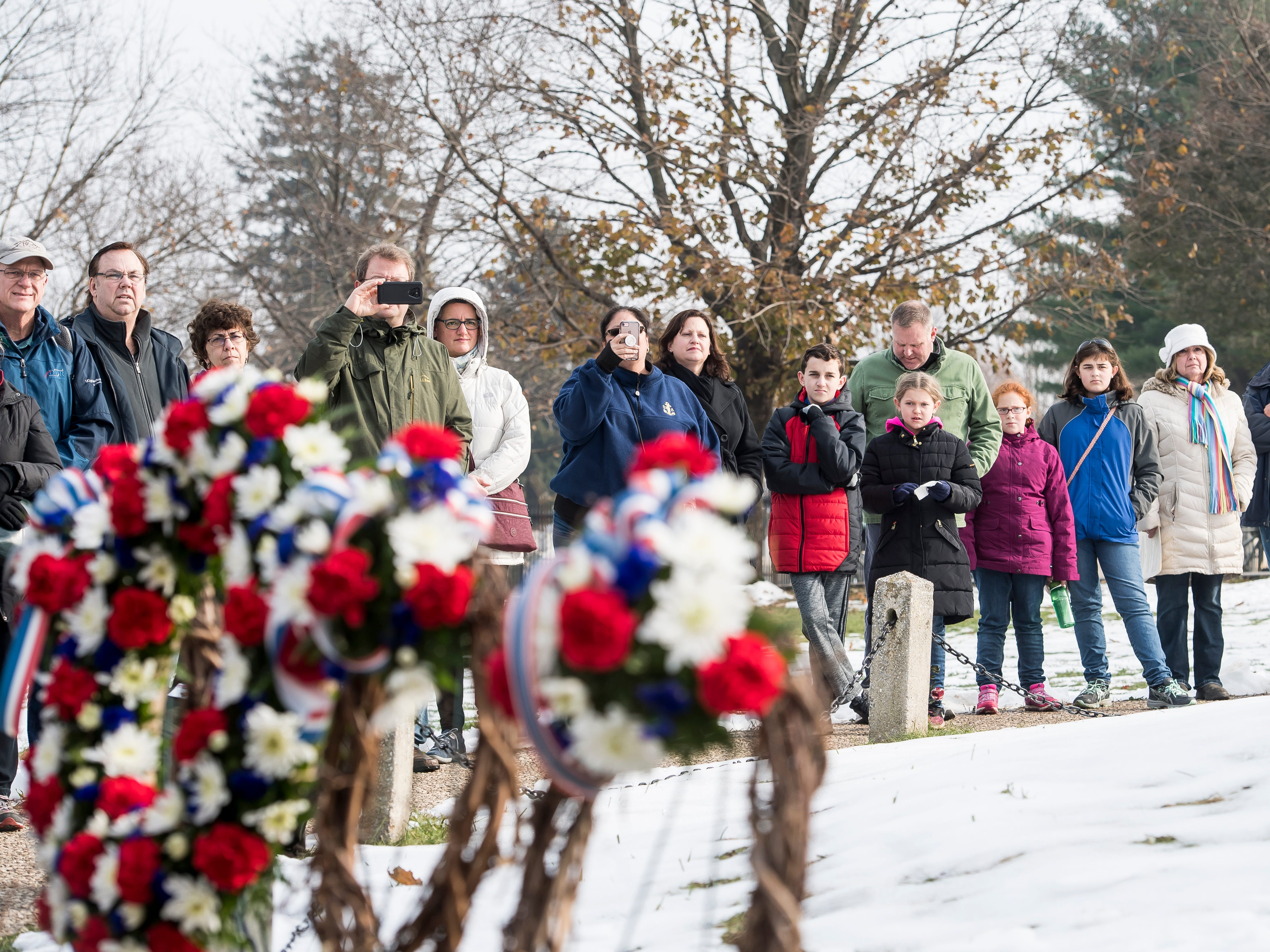 People wait for the start of the laying of memorial wreaths ceremony at Soldiers' National Monument in Gettysburg National Cemetery on November, 19, 2018.