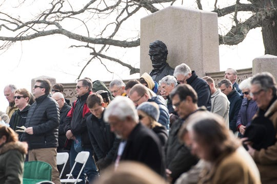 People bow their heads as the the invocation is delivered at the start of Dedication Day in Gettysburg on November, 19, 2018. The day marked the 155th anniversary of Abraham Lincoln's Gettysburg Address. Lincoln's Gettysburg Address Memorial stands in the background.