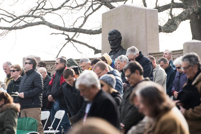 People bow their heads as the Reverend Dr. Charles Teague delivers the invocation at the start of Dedication Day in Gettysburg on November, 19, 2018. The day marked the 155th anniversary of Abraham Lincoln's Gettysburg Address.