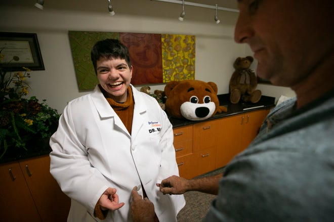Volunteer Victor Hickman helps Selima Martin, a patient transporter with Banner Desert and Cardon Children's Medical Center get into the Dr. Bear mascot costume at Cardon Children's Medical Center in Mesa on Friday, November 16, 2018. Martin, who has Asperger's syndrome  was on the team to come up with the idea for Dr. Bear, the Cardon Children's Medical Center mascot. She volunteers as the mascot and visits children at Cardon Children's Medical Center.
