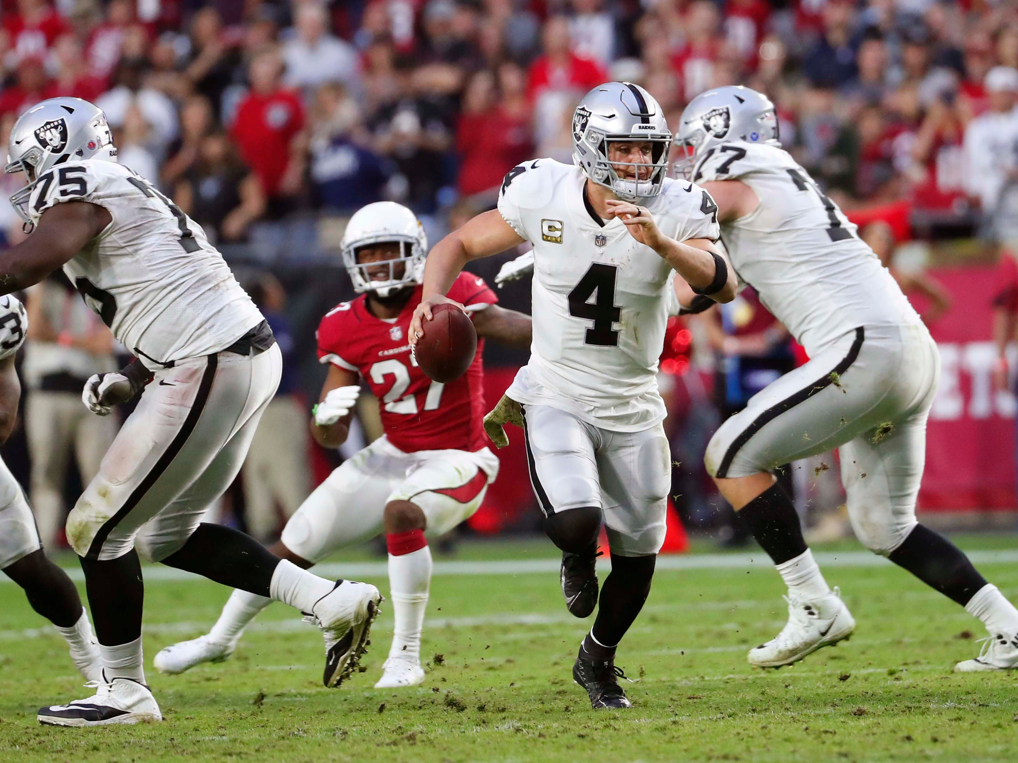 Oakland Raiders quarterback Derek Carr (4) scrambles away from pressure against the Arizona Cardinals during the fourth quarter Nov.18th at State Farm Stadium.