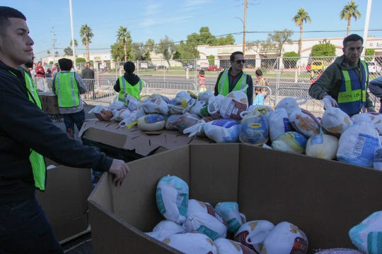 St. Mary's Food Bank volunteers give out turkeys during the three-day Thanksgiving food drive in Phoenix on Monday, Nov. 19, 2018.