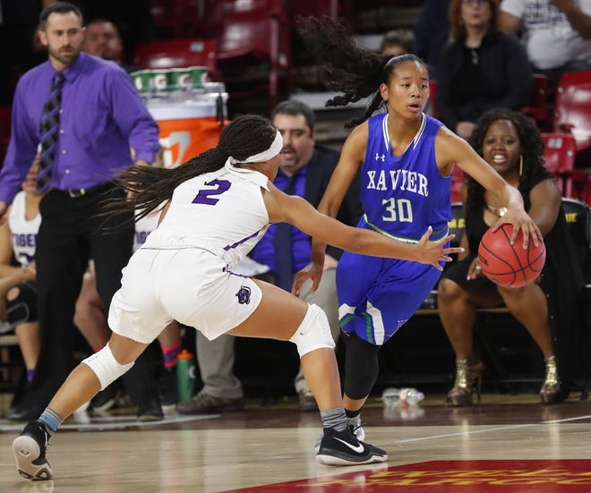 Xavier's Leilani McIntosh is pressured by Millennium's Jasmine Singleton during the 6A girls basketball semifinal Feb. 21 at Wells Fargo Arena.
