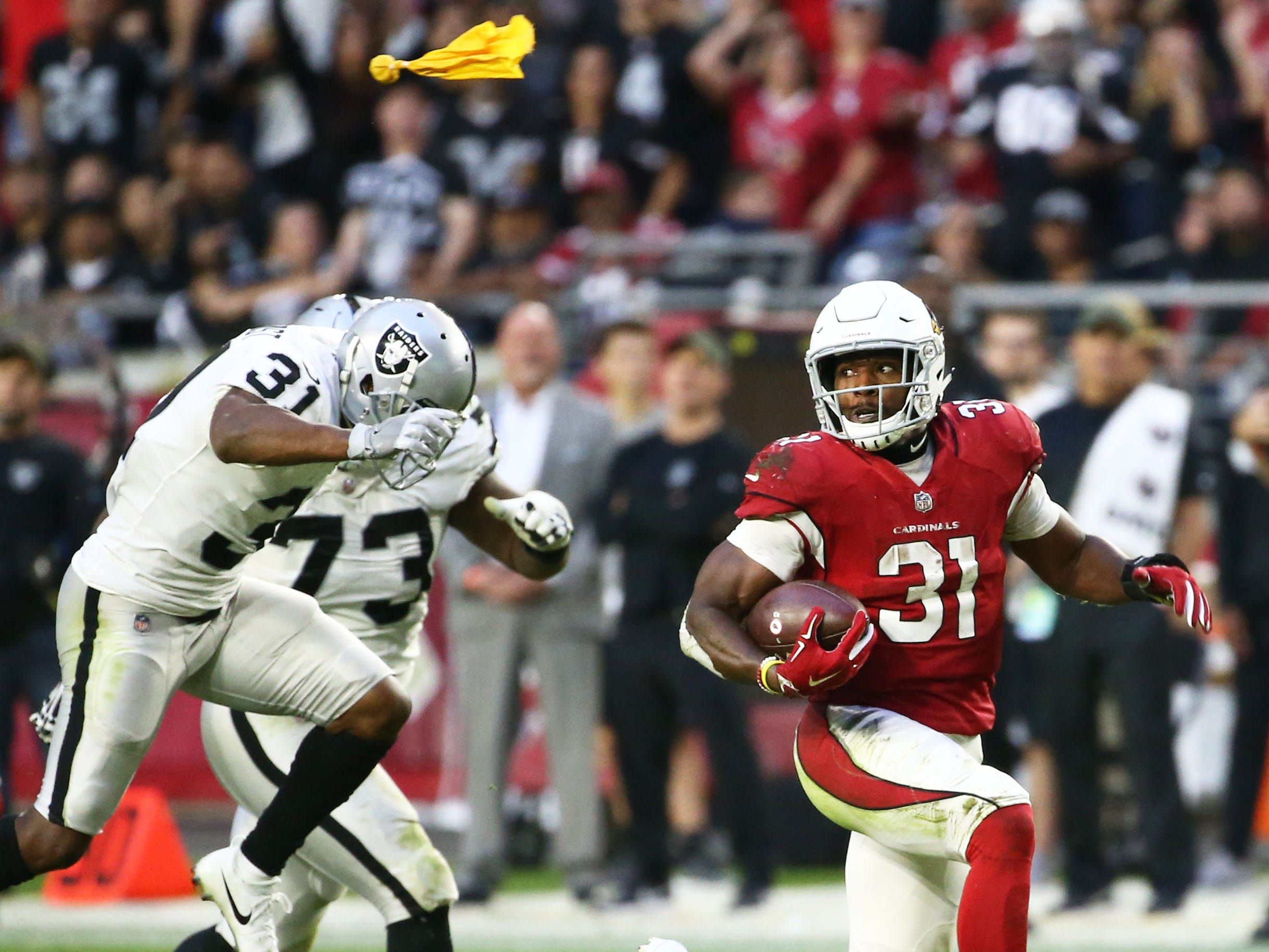 A flag (top) flies over Arizona Cardinals running back David Johnson as he runs for a touchdown against the Oakland Raiders in the second half during a game on Nov. 18 at State Farm Stadium. The touchdown has called back due to offensive holding against the Cardinals.