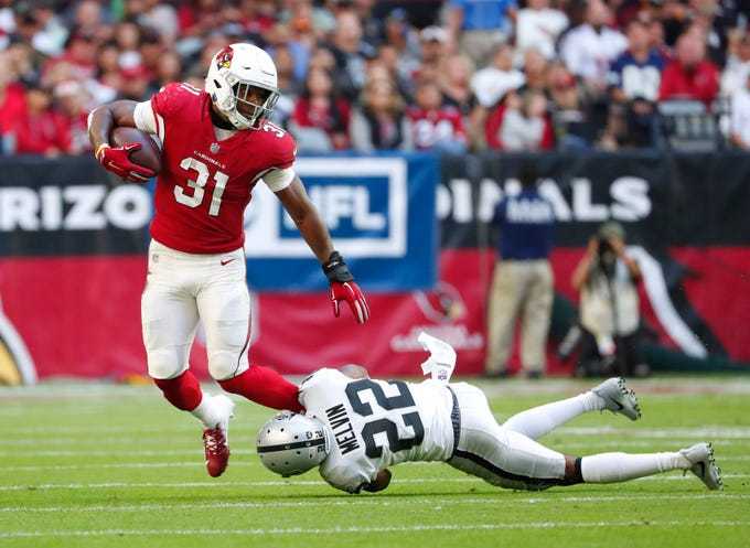 Arizona Cardinals running back David Johnson (31) is brought down by Oakland Raiders cornerback Rashaan Melvin (22) during the first quarter Nov. 18th at State Farm Stadium.