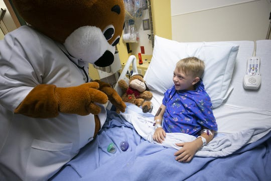 Dressed as Dr. Bear, the Cardon Children's Medical Center  mascot, Selima Martin, a patient transporter with Banner Desert and Cardon Children's Medical Center cheers up Tucker Richards, 7, of Gilbert, at Cardon Children's Medical Center in Mesa on Friday, November 16, 2018. Martin, who has Asperger's syndrome  was on the team to come up with the idea for Dr. Bear, the Cardon Children's Medical Center mascot. She volunteers as the mascot and visits children at Cardon Children's Medical Center.