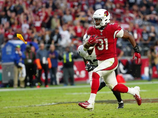 Arizona Cardinals running back David Johnson (31) runs for a touchdown against the Oakland Raiders while a penalty flag is thrown during the fourth quarter Nov. 18th at State Farm Stadium. His touchdown was called back because of a holding penalty.