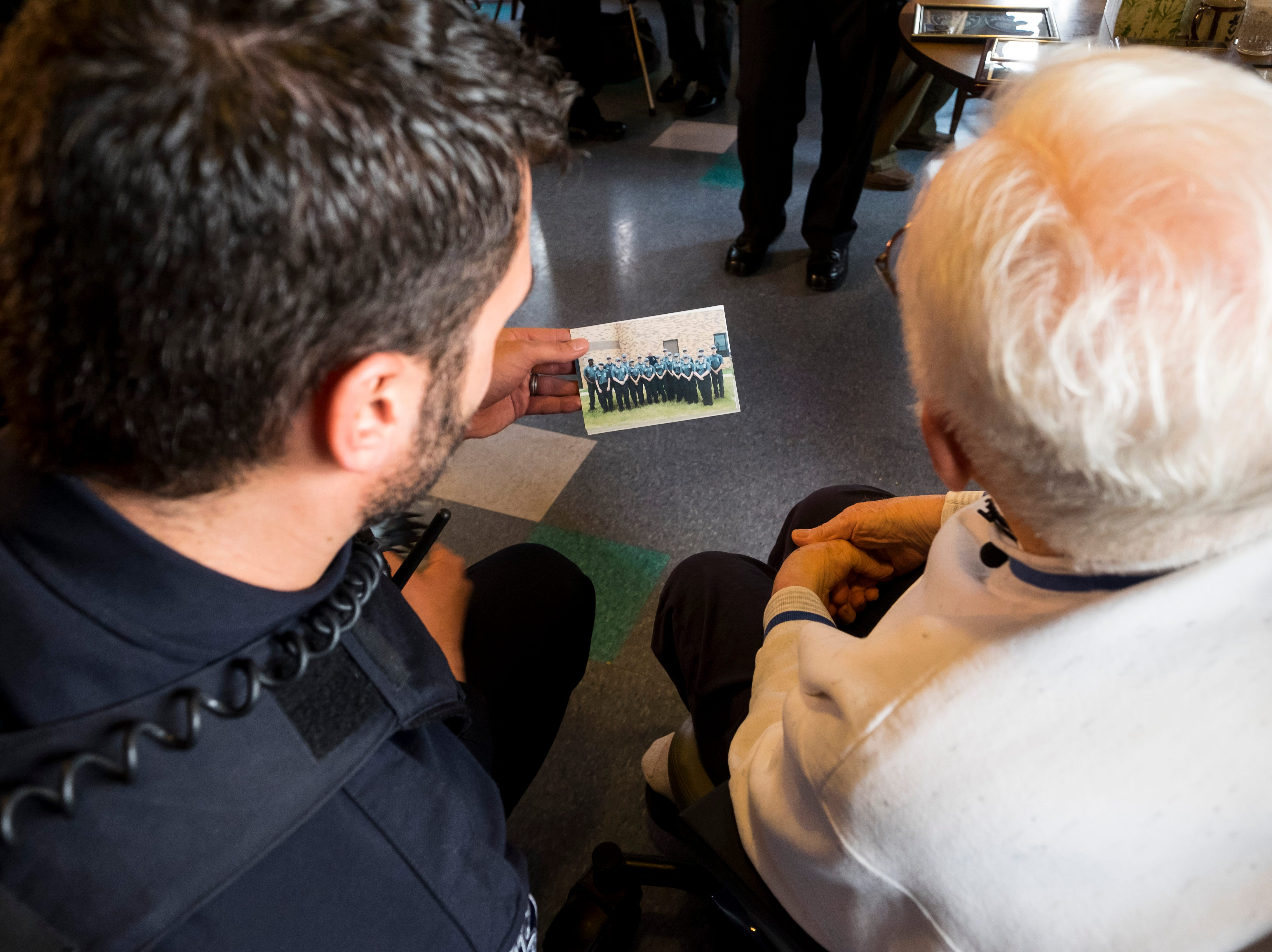 Port Huron Police Officer Dennis Huisman, left, shows photos of the department's first graduating Youth Police Academy class to William Turney after a recognition ceremony Monday, Nov. 19, 2018.