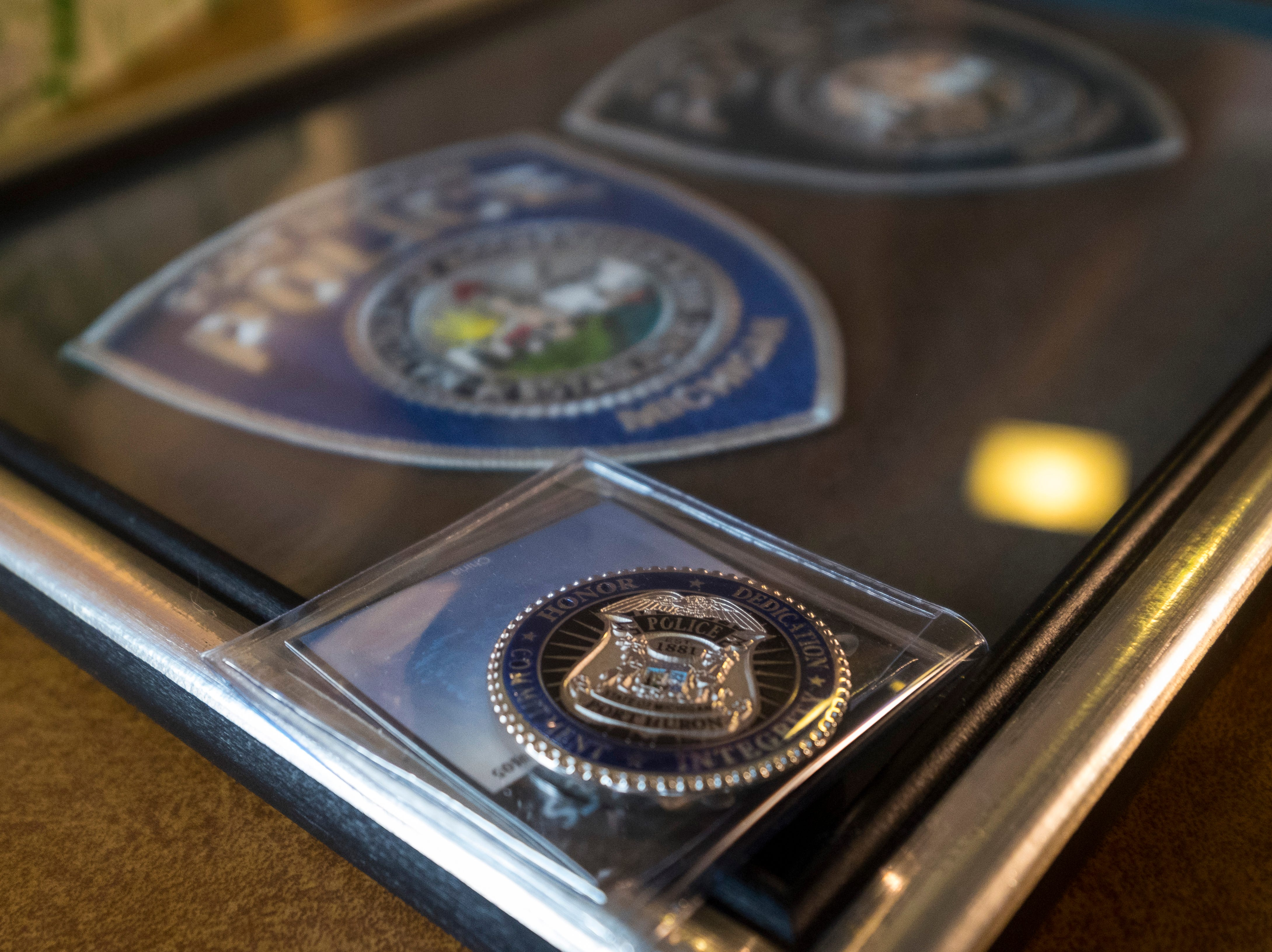 A Port Huron Police challenge coin and two framed patches sit on a table after being presented to William Turney, a 92-year-old World War II veteran who wanted to become a police officer after the war.