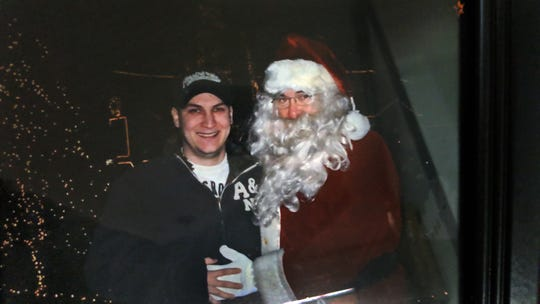 Donnie Webb, right, poses as Santa with his son Seth in this photo taken prior to Seth's death in 2015. Webb said that his son originally inspired the Christmas display.