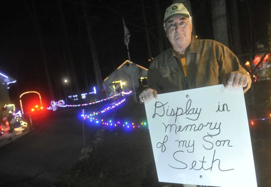"Donnie Webb with a sign dedicating his 2015 holiday display in memory of his son Seth. Webb lost his son, Seth, in a car accident two months earlier. ""And now I lost my reason for my Christmas,"" said Webb, who chose to continue the annual tradition to remember the son who inspired him to do it in the first place."