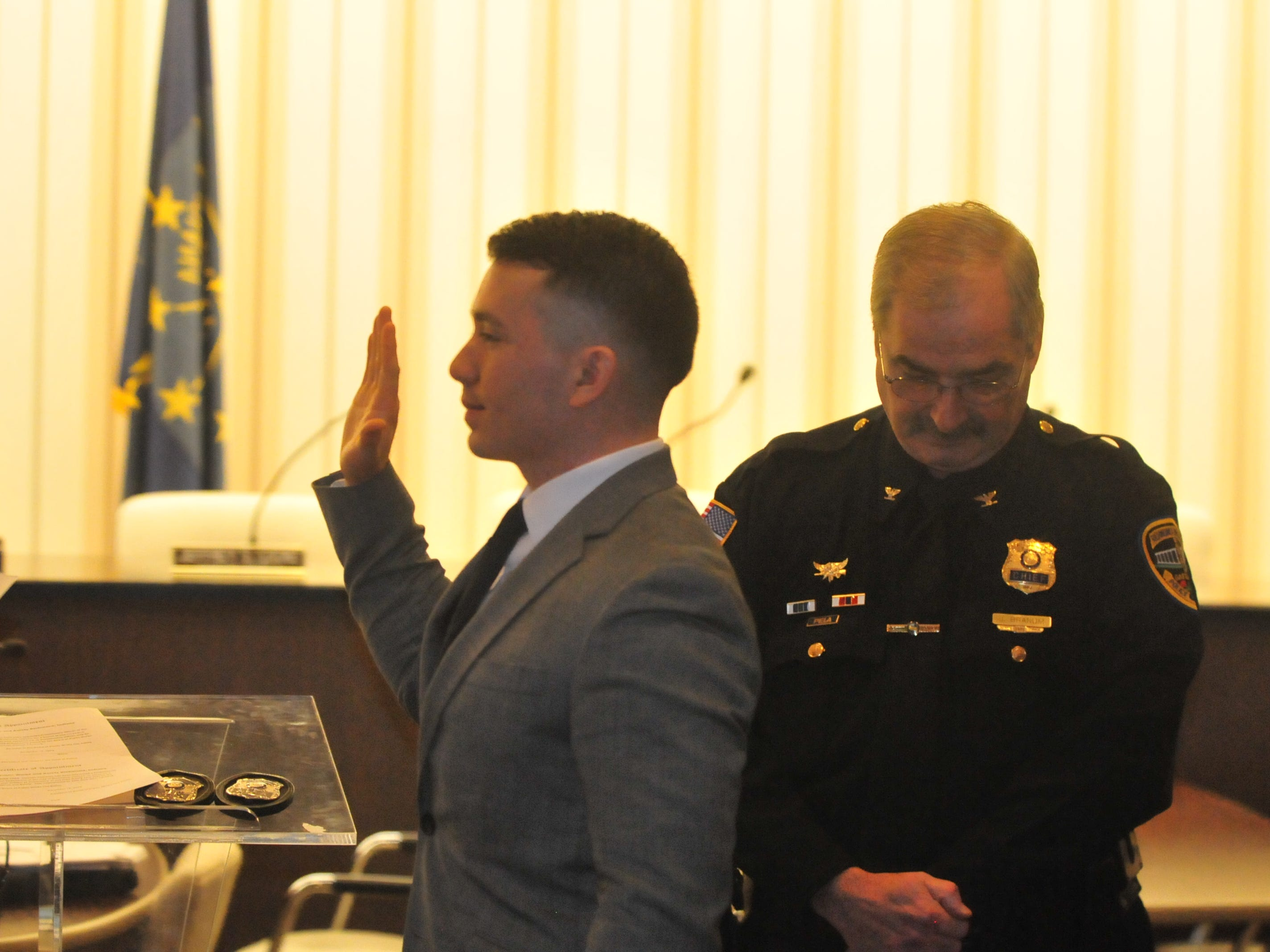 Joshua Anicete is sworn in Monday as a new Richmond Police Department officer as Chief Jim Branum listens.