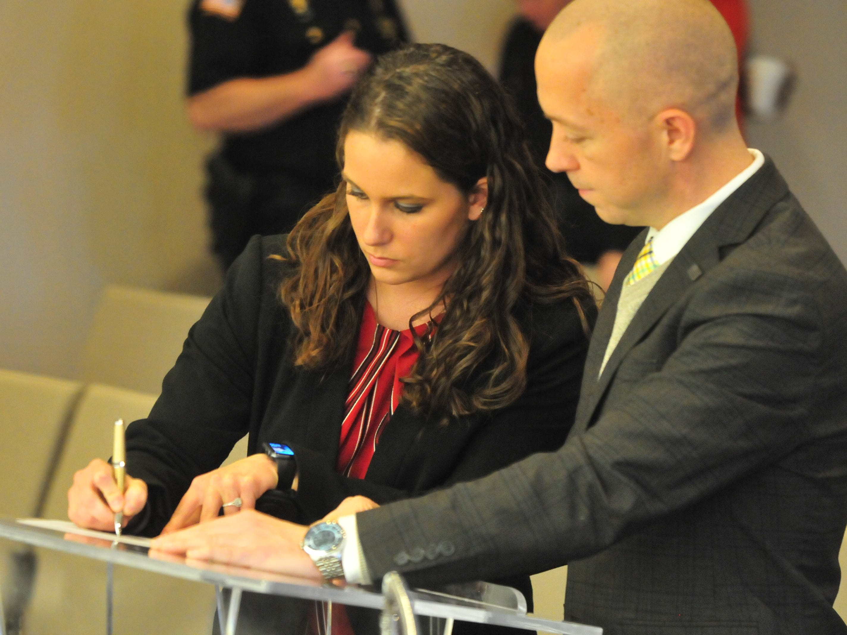 Amanda Thackrey signs paperwork with Mayor Dave Snow after Snow swore Thackrey in as a Richmond Police Department officer Monday.
