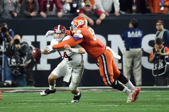 Alabama Crimson Tide quarterback Jake Coker (14) is sacked by Clemson Tigers defensive end Shaq Lawson (90) during the second quarter in the 2016 CFP National Championship.