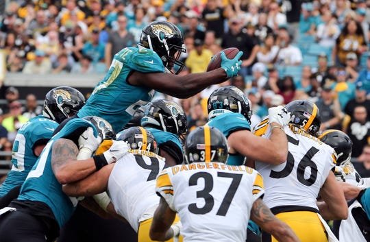 Jacksonville Jaguars running back Leonard Fournette, top, dives over the Pittsburgh Steelers defense, including Jordan Dangerfield (37) and Anthony Chickillo (56), to score a touchdown during the second half of an NFL football game, Sunday, Nov. 18, 2018, in Jacksonville, Fla. (AP Photo/Gary McCullough)
