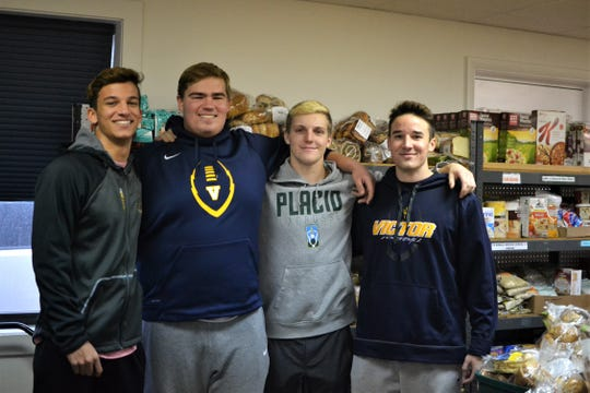 From left: Kordell Jackson, CJ Williams, Sutton Boland and Hudson Alread stop by the Victor/Farmington Food Cupboard to drop off donated food they collected. All four are seniors and play for Victor High School's varsity football team.