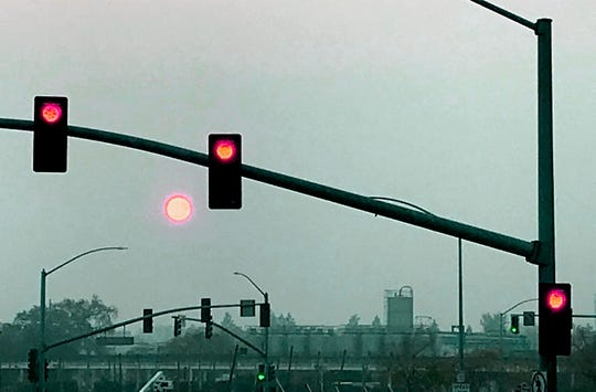 Smoke from the Camp Fire obscures the sun Saturday with stop lights in the foreground and the Sierra Nevada brewery in the background. Sierra Nevada Brewing Co. is joining with the city of Paradise, World Central Kitchen, Chico State University and its students to serve Thanksgiving meals to fire evacuees on Thursday.