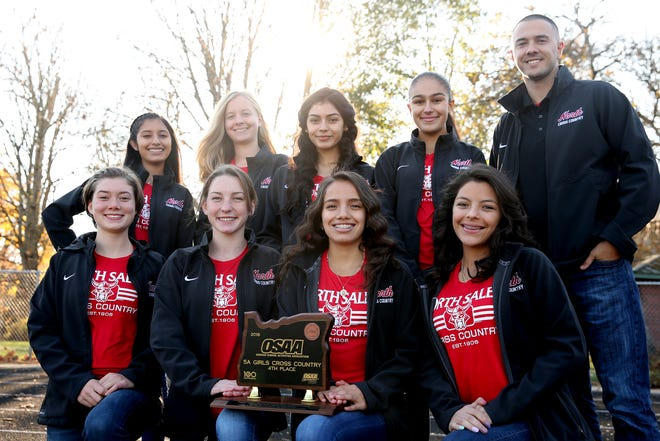 The North Salem girls cross country team, front row from left, Abi Swain, Emmalee Haburn, Eimy Martinez, Brianna Marquez, back row from left, Geyssa Sandoval, Isa Swain, Perla Quevedo, Elia Sanchez, and head coach Michael Herrmann at North Salem High School on Monday, Nov. 19, 2018. The North Salem girls cross country team placed fourth in the 5A state meet, earning the school's first trophy at the state meet.