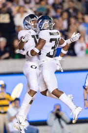 Oregon's Dillon Mitchell (13) celebrates with Jaylon Redd (30) earlier this season at California. The Ducks play the Beavers this week in the Civil War.
