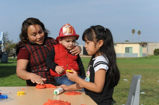 In this file photo, a mother shows her son how to play with Play-Doh as a young girl makes shapes at the First 5 Monterey County and Alisal Union School District-partnered booth during an Alisal Family Resource Center festival.
