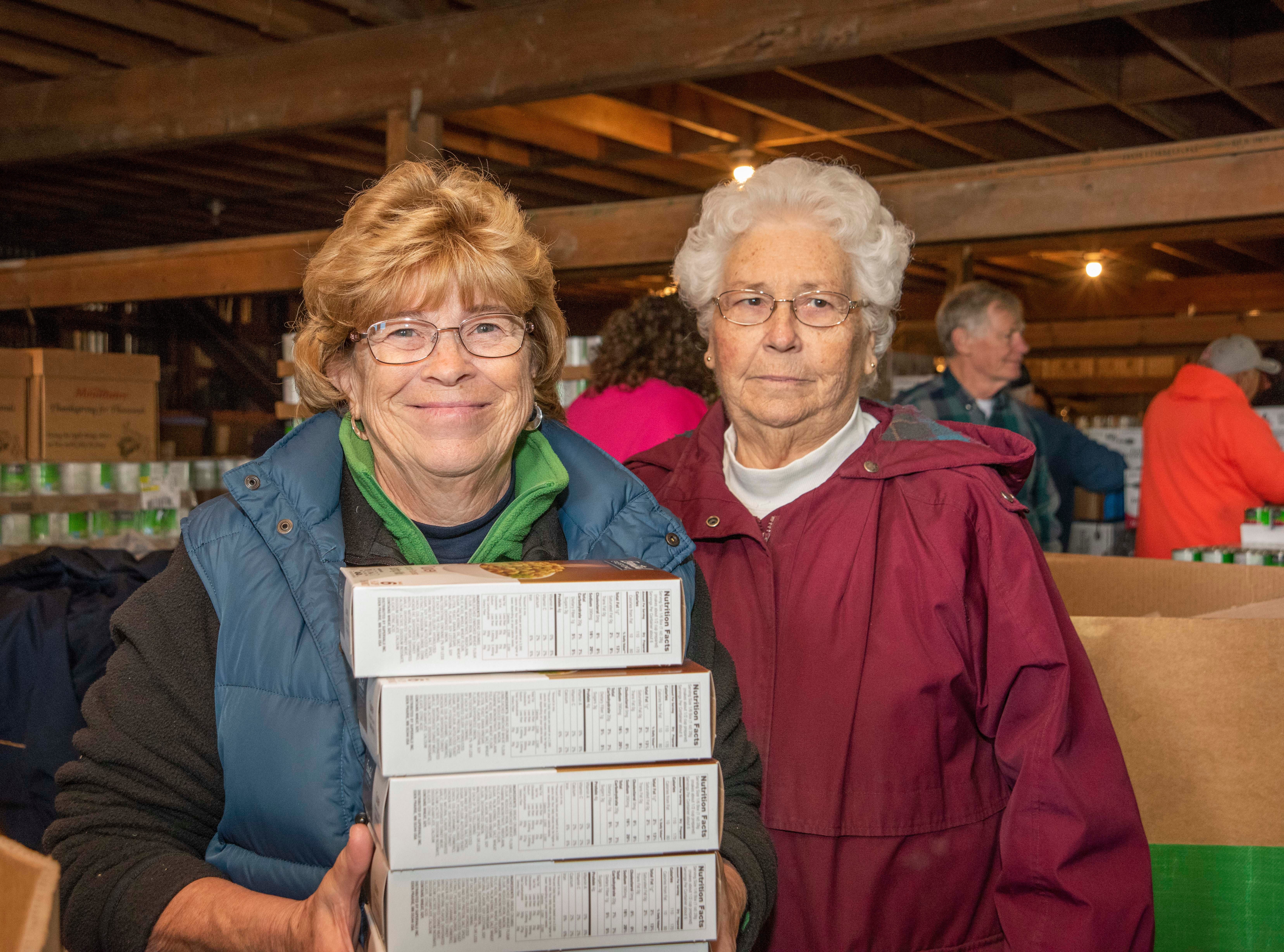 (L) Joanne Schmitt and Barbara Sapp, members of the Delaware Farm Bureau help pack boxes of food for Thanksgiving for Thousands.
