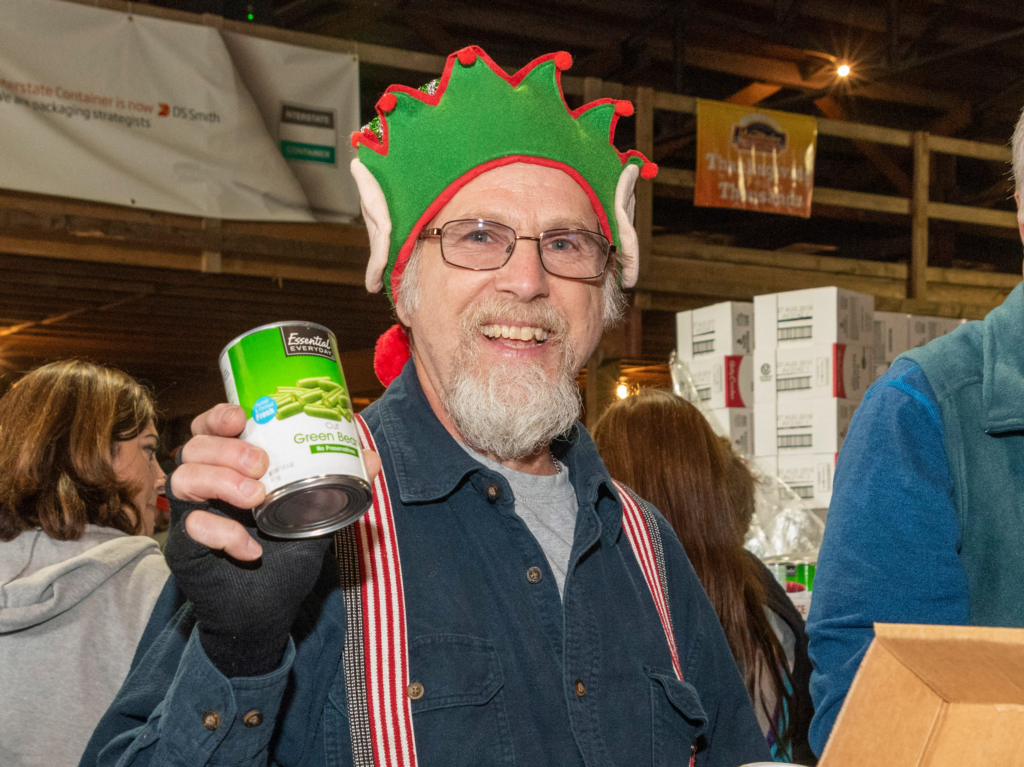 """Elf"" Dave Vicino brought lots of holiday spirit Monday morning to Mountaire, Selbyville - packing boxes of holiday food for Thanksgiving for Thousands."