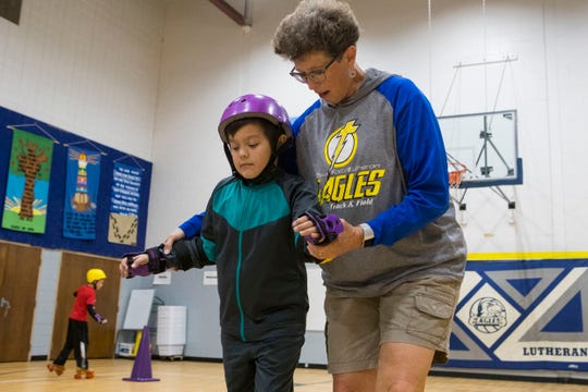 Melanie Nelson, physical education teacher, teaches Tristan Feldhaus how to skate Monday, Nov. 19, 2018 at Sioux Falls Lutheran School in Sioux Falls, South Dakota.
