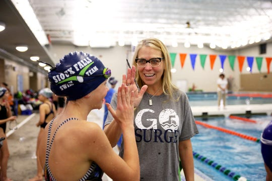 Paula Gordon, an assistant coach for the Sioux Falls swim team and Jack Gordon's mother, high fives one of her swimmers at the Sioux Falls Swim Team Hurricane Michael Relief Meet Nov. 16.