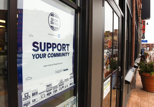 Local businesses are promoting shopping local this holiday season with signs in their windows shown Monday, Nov. 19, in St. Cloud.