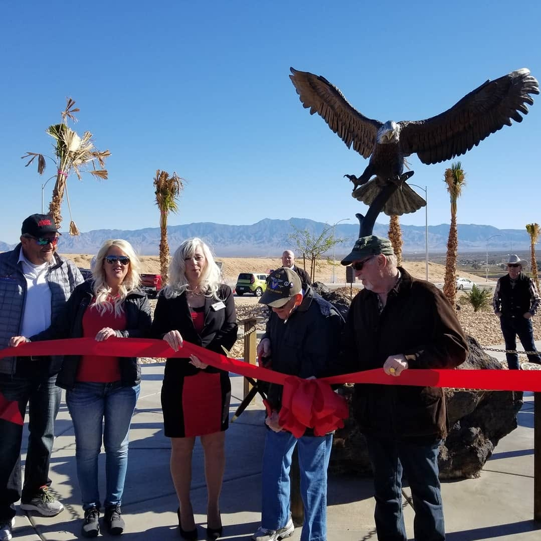 Mesquite Chamber of Commerce CEO Carol Kolson and Mesquite mayor Al Litman help veteran Lt. James F. Miller cut the ribbon at the ceremony commemorating the new Eagles Landing Veterans Memorial.