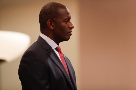 Former Mayor Andrew Gillum listens as City Manager Reese Goad gives a speech about him during the Tallahassee City Commission reorganization meeting Monday, Nov. 19, 2018.