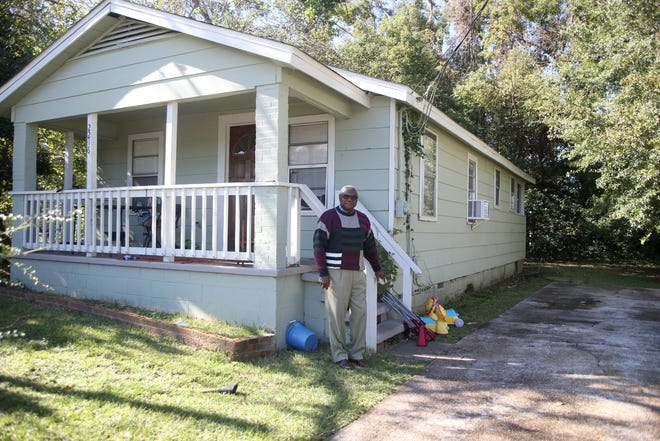 Dr. Henry Lewis, a former pharmacy school dean at FAMU, poses for a photo outside his childhood home located on Saxon Street, Friday, Nov. 16, 2018.